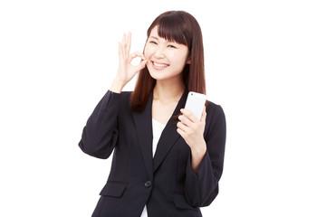 スマートフォンを持ってOKサインするビジネスウーマン