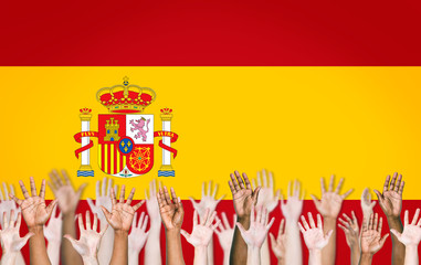 Group of Arms Raised and Spanish Flag as Background