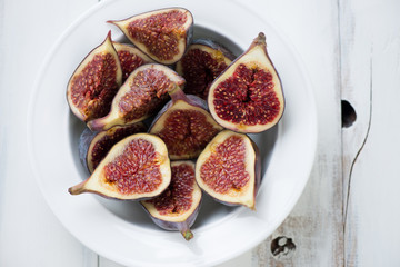 Close-up of sliced fig fruits in a glass plate, above view