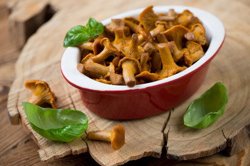 Pickled chanterelles with green basil over wooden background