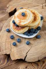 Homemade fritters with blueberries over rustic wooden surface