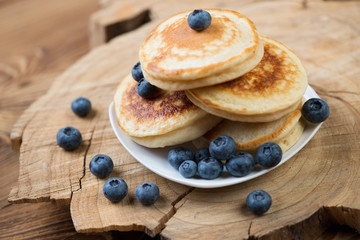 Pancakes with blueberries over rustic wooden background