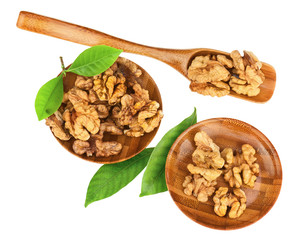 Handful of walnuts in wooden bowls, scoop and green leaves.