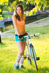 Portrait of a beautiful young woman with her bike outdoor