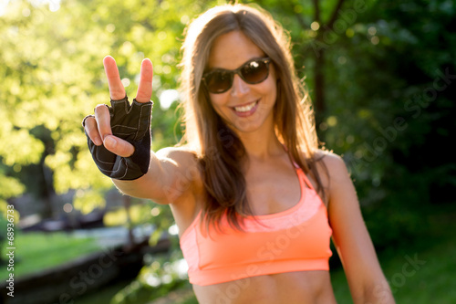 canvas print picture lovely young woman showing victory or peace sign during sport