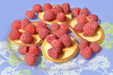 Оладьи с ягодой на синей тарелке.
