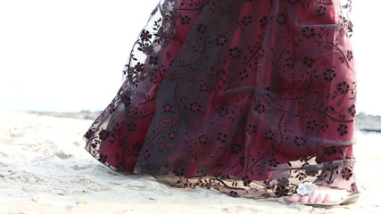 burgundy dress developing in the wind on a woman that stands in