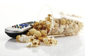 Popcorn im Plastikbecher neben Fernbedienung