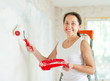 woman paints wall with roller