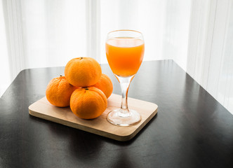 Glass of freshly pressed orange juice with four orange
