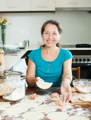 Mature woman making dumplings from meat