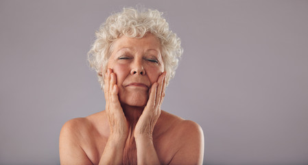 Senior woman pampering her face