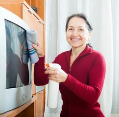 Ordinary mature woman dusting TV