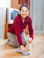 Smiling mature woman rubing parquet floor