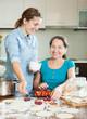 Two  women making sweet vareniki with berries