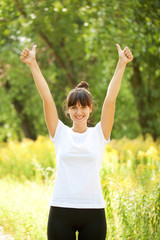 Woman in white t-shirt showing a thumbs up sign outdoors. Ready