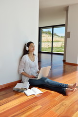 relaxed young woman at home working on laptop