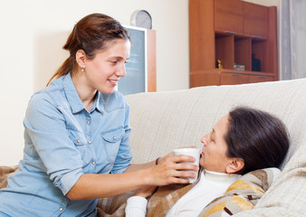 woman caring for sick mature mother  at home