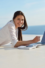 relaxed young woman at home working on laptop computer