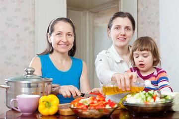 women with baby girl cook veggie lunch