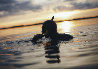 Young adult snorkeling in sea during sunset