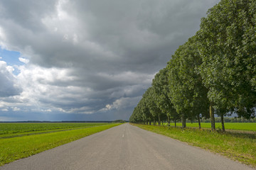 Clouds over a road through the countryside