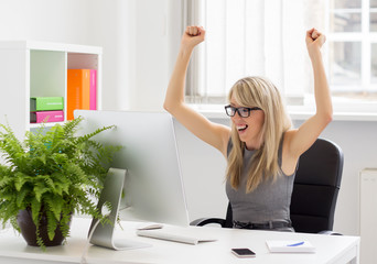 Happy woman sitting at her desk with arms up