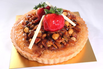 Mixed nuts pie decorated with strawberry.