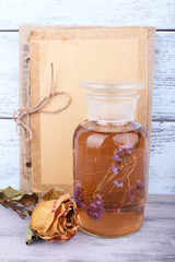 Bottles of herbal tincture, book and dried rose