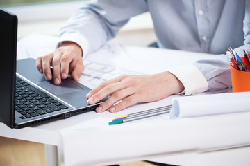 Close-up of architect working on laptop