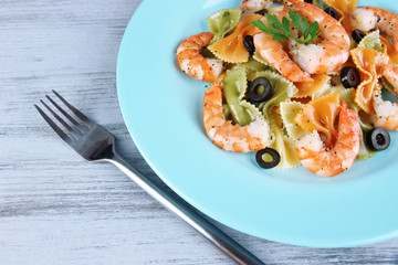 Fresh prawns with coloured macaroni, olives and parsley in a