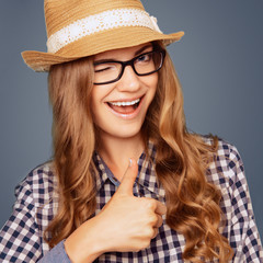 portrait of a smiling young woman with casual garb winking and