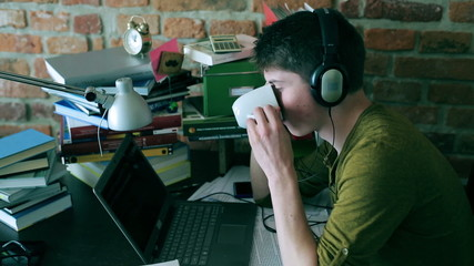 Student listening music on headphones and drinking coffee