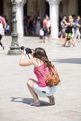 Young girl photographer taking photo