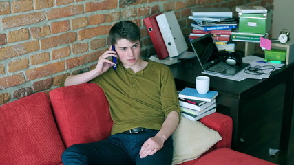 Student resting on red sofa and chatting on cellphone