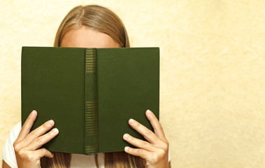 Girl holding a book and closes her face