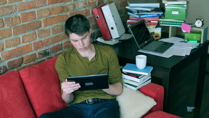 Man working on tablet and sitting on red sofa in the room