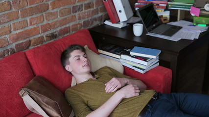 Man coming home after rough day at work and relaxing on red sofa