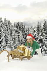 Junge Frau schiebt Schlitten mit WeihnachtsGeschenk,schenkenen