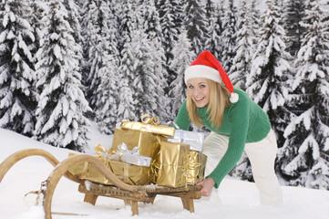 Junge Frau schiebt Schlitten mit Weihnachtspäckchen