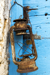Rusted oil lamp. Blue wooden door in the background