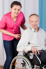 Senior on wheelchair and nurse