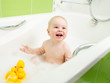 smiling toddler boy taking bath and playing with toys
