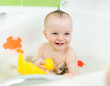 smiling baby taking bath and playing with toys
