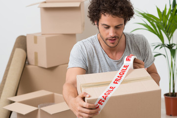 Young Man Packing Cardboard Box