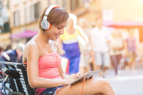 canvas print picture Beautiful Girl with Headphones and Digital Tablet in the City