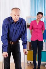 Elder man using crutches