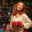 young woman holding red gift over christmas tree and lights on b