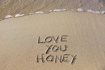 Love you honey written on the beach.