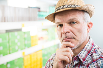 Farmer at supermarket with hand on chin